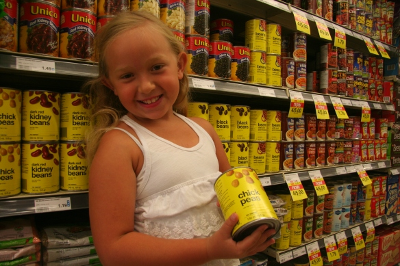 Claire holding up a can of tuna and a can of beans