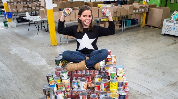 Sarah sitting on a mountain of cans at the Daily Bread Food Bank